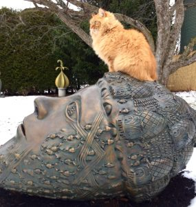 Leslie Fry's Henry, who has his own Facebook page, enjoys the chance to stand guard in the artist's sculpture garden.
