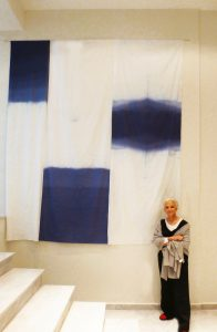 Marietta Patricia Leis with fabric hangings at the Ionian Center for the Arts and Culture