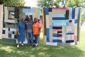 Mary Lee Bendolph, with two of her children, Rubin Bendolph Jr. and Essie Bendolph Pettway, stand in front of quilts by Essie. Photo: Andrea Packard