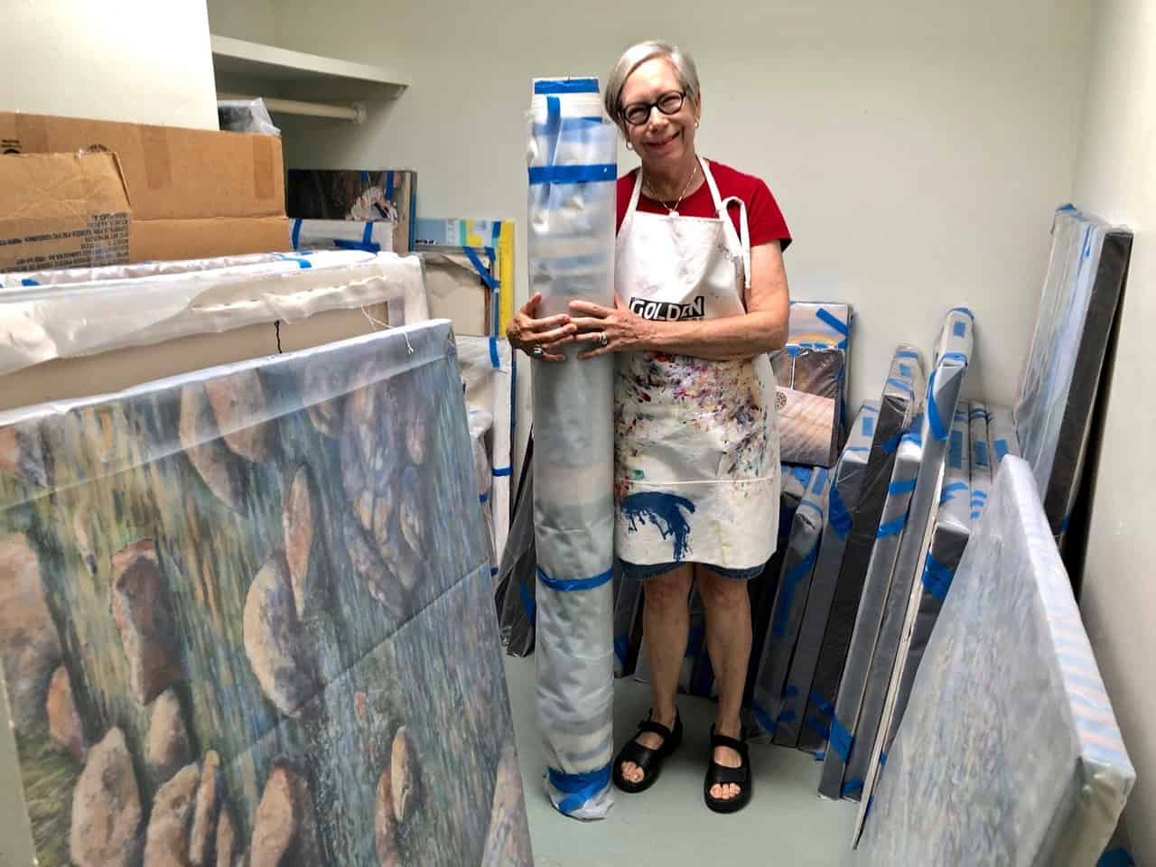 Barbara Kemp Cowlin with a roll of canvases and paintings under wraps in a storage closet