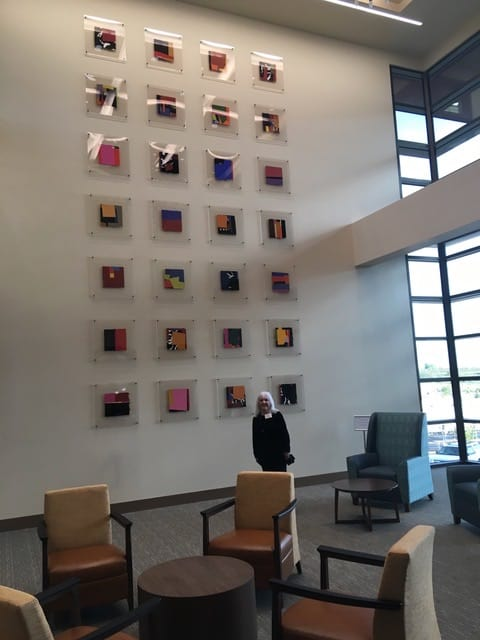 Annell Livingston with a wall of her gouaches at Santa Fe Presbyterian Hospital